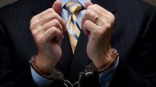 Man in suit wearing handcuffs