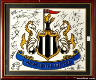 A Newcastle United crest signed by multiple players