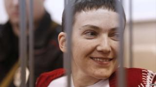 Ukrainian air force officer Nadezhda Savchenko smiles as she stands inside a defendant's cage during her hearing at the Basmanny district court in Moscow on 10 February 2015