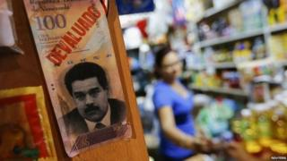 "President Nicolas Maduro and the word ""devaluated"" is seen at a market in Caracas February 13, 2015."