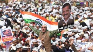 Supporters of the Aam Aadmi Party (AAP) shout slogans as they watch leader Arvind Kejriwal being sworn in as Delhi chief minister at Ramlila Grounds in New Delhi on Saturday