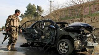 A member of the Afghan security forces inspects the site of a bomb blast targeting the vehicle of Angeza Shinwari, member of the Provincial Council of Nangarhar province, in Jalalabad, Afghanistan, 10 February 2015.