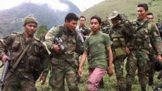 Soldiers escort a 13-year-old captured teenage rebel of the Farc in the mountains of Santander state on 21 December, 2000.