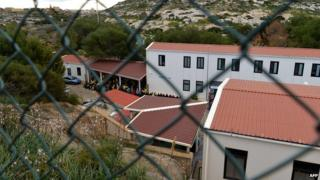 """A picture taken through a fence shows migrants at the """"Temporary Permanence Centre"""" (CPT), a refugee camp on Lampedusa on 17 February 2015"""