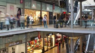People walk in the shopping gallery of the Gare Saint Lazare railway station in Paris on 30 March 2012