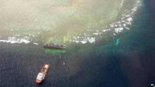 This photo, released by the Tubbataha Management Office, shows an aerial view of the U.S. Navy minesweeper USS Guardian, top, stranded in the Tubbataha Reef - 25 January