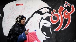 "A woman walks past graffiti reading ""revolution"" in Arabic in December 2011"