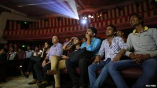 """Cinema goers watch Bollywood movie """"Dilwale Dulhania Le Jayenge"""" (The Big Hearted Will Take the Bride), starring actor Shah Rukh Khan, inside Maratha Mandir theatre in Mumbai December 12, 2014"""