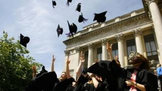 Graduates celebrating by throwing their mortaboard hats in the air