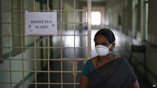 An Indian security woman covers her face with a mask outside the swine flu ward of Gandhi Hospital in Hyderabad, Feb 20