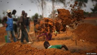 A grave digger works at a US-built cemetery on 27 January 2015 in Disco Hill, Liberia