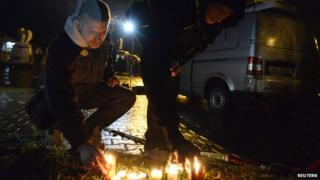 People light a candle near a restaurant where a gunman opened fire in Uhersky Brod, February 24, 2015