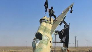Fighters of the Islamic State wave the group's flag from a damaged display of a government fighter jet following the battle for the Tabqa air base, in Raqqa, Syria