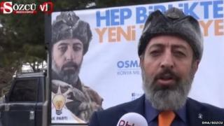 Osman Yavuz standing in front of his campaign poster