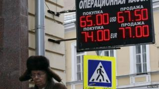 A woman walks near a board displaying currency exchange rates in Moscow