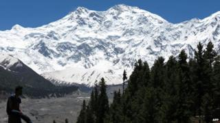 In this photograph taken on August 7, 2014 a sign points towards a view of Nanga Parbat