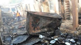 People inspect damaged shops following a bomb explosion at a Market in Bauchi, Nigeria (December 2014)