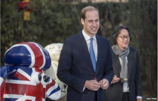 """Britain's Prince William, Duke of Cambridge, poses after painting the eye of a """"Shaun the Sheep"""" sculpture at the British Ambassador's official residence in Beijing, 2 March 2015"""