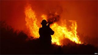 A firefighter tries to stop a blaze in Noordhoek Manor old age home, Cape Town, South Africa, 02 March 2015