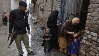 A police man watches on as a Pakistani health worker gives a polio vaccine to a child in Peshawar, Pakistan. 16 February 2015