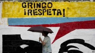 "A woman using an umbrella during a drizzle walks by a mural representing the eyes of Venezuela's late President Hugo Chavez that reads in Spanish ""Gringo, respect!"" in Caracas, Venezuela, Monday, March 2, 2015."