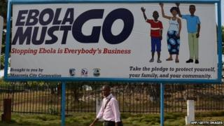 """A man walks past an Ebola campaign banner with the new slogan """"Ebola Must GO"""" in West Africa on 23 February 2015."""