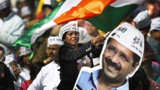 A supporter of Aam Aadmi Party next to a cut-out of party leader Arvind Kejriwal February 14
