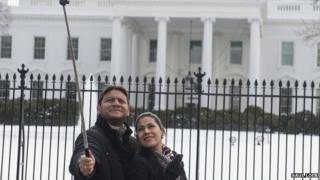 Couple take photo with selfie stick in front of the White House