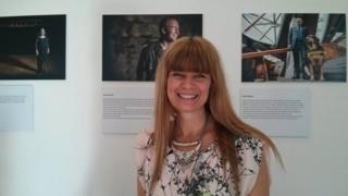 Photographer Trudy Stade stands in front of her portrait of Jamie MacDonald