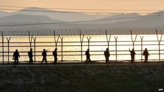 South Korean soldiers patrol along a military fence near the Demilitarized Zone (DMZ) dividing the two Koreas in the border city of Paju on April 26, 2013.
