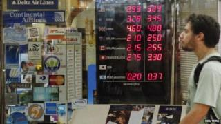 Man walks past board showing currency rates