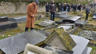Members of the Jewish community look at broken tombstones after a ceremony at the Jewish cemetery in Sarre-Union