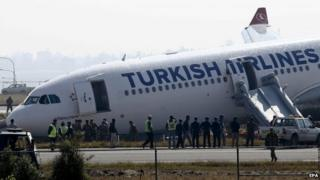 Nepalese emergency officials inspect a Turkish Airlines airbus after it skidded off from the runway at Tribhuvan International Airport in Kathmandu, Nepal on 4 March 2015