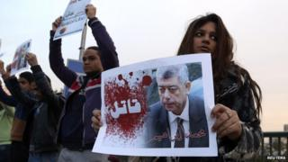 "A protester holds a poster of Interior Minister Mohamed Ibrahim with the word ""Killer"" on it during a silent protest over a bridge in Cairo, 14 February 2015."
