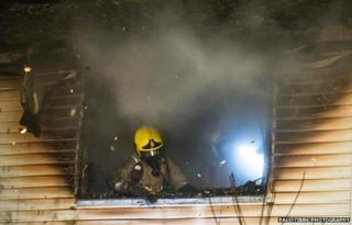 Firefighter in upstairs window of Winston Churchill Drive property
