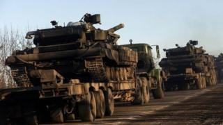 Military trucks from the Ukrainian armed forces transport tanks on the road near Artemivsk, eastern Ukraine, 24 February 2015