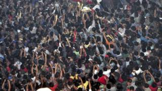 In this Thursday, March 5, 2015 photo, members of a mob raise their hands to take photos of a man, top centre, accused of rape after he was lynched and hung in the city landmark Clock Tower in Dimapur, in the north-eastern Indian state of Nagaland