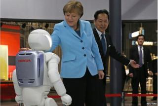 """German Chancellor Angela Merkel (C), escorted by Mamoru Mori, executive director of the museum and former astronaut, touches """"Asimo"""", a bi-ped humanoid robot developed by Honda Motor Co., while visiting Miraikan (National Museum of Emerging Science and Innovation) in Tokyo 9 March 2015."""