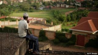 Man sitting on a roof overlooking Kigali