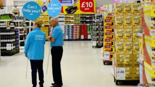Tesco workers stand in supermarket