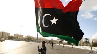 A man holding the Libyan flag