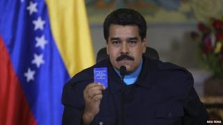 President Nicolas Maduro holds up a copy of the country's constitution as he speaks during a national TV broadcast in Caracas on 9 March 2015