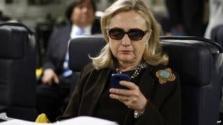 then-Secretary of State Hillary Rodham Clinton checks her Blackberry from a desk inside a C-17 military plane upon her departure from Malta, in the Mediterranean Sea, bound for Tripoli, Libya 18 October 2011
