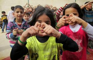 Children making heart signs instead of V for Victory signs
