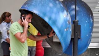 A Cuban talks by phone in a street of Havana on March 11, 2015.
