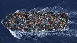 A boat packed with refugees tries to cross the Mediterranean