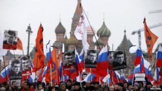 """People hold flags and posters during a march to commemorate Kremlin critic Boris Nemtsov near St Basil""""s Cathedral in central Moscow"""