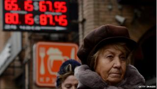 Woman walking in front of exchange rate sign
