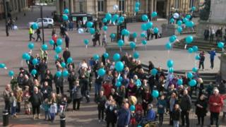 People releasing blue balloons