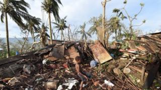 Young boy picks through the debris in Port Vila, Vanuatu after Cyclone Pam - Monday, March 16, 2015